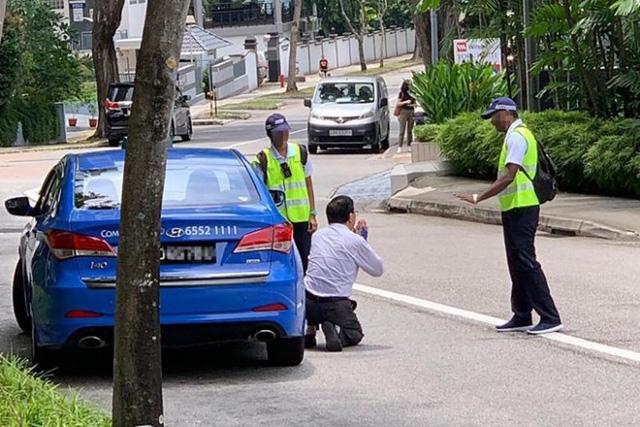 Tài xế taxi Singapore quỳ gối xin tha khi bị phạt vì hút thuốc lá - Ảnh 1.